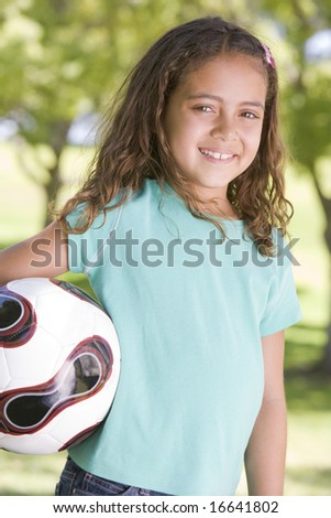 Young girl holding soccer ball outdoors smiling