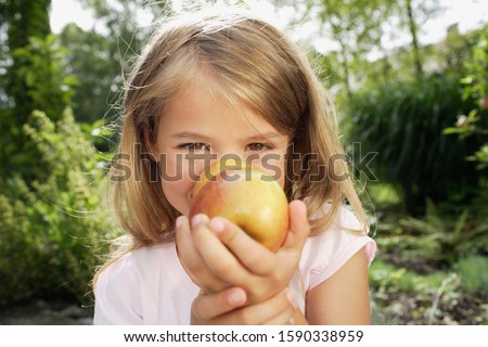 Young girl holding two apples
