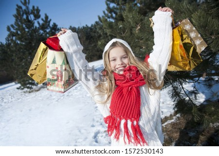 Young girl holding up Christmas presents, portrait