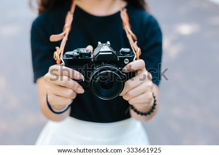 young girl holding vintage film camera #333661925
