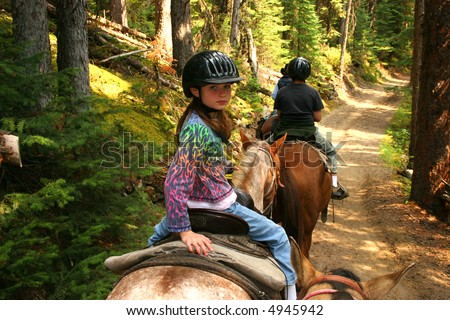 Young girl horseback riding along forest trail.