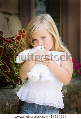 young girl hugging a plush bunny - stock photo