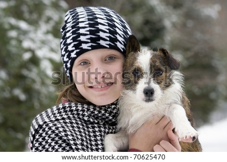 Young girl hugging her cute puppy outside in the snow