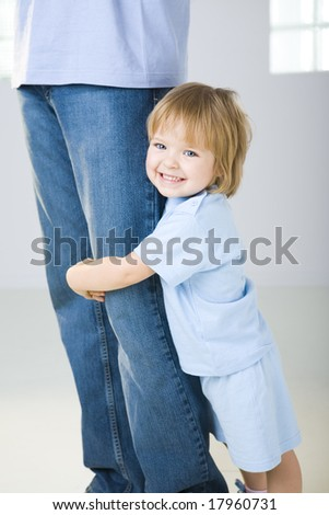 Young girl hugging man's leg. She's looking at camera. Focused on young girl.