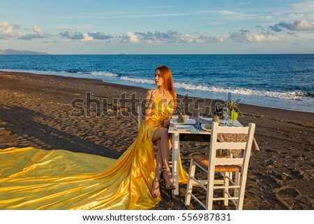 Young girl in a beautiful yellow dress with a train, sitting at a table on the seafront #556987831