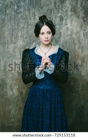 Young girl in a blue dress. Historical costume.