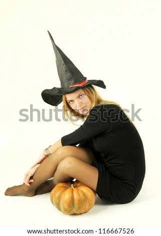 young girl in a carnival witch costume with a halloween pumpkin isolated on the white background