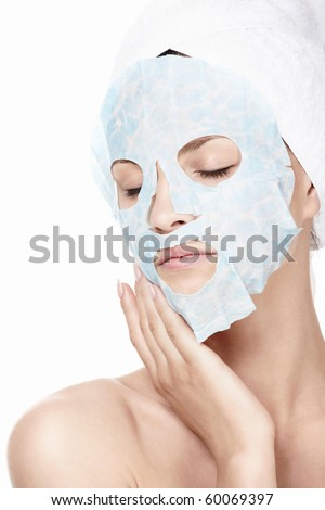 Young girl in a cosmetic mask on a white background