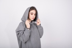 Young girl in a gray sweatshirt with a hood on her head . High quality photo