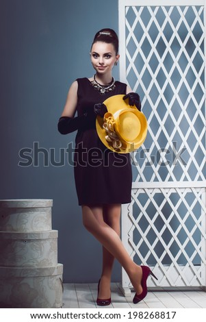 Young girl in a little short black dress holding a yellow hat in hand, long black gloves, hat boxes in studio. Surprised Luxury Lady.Image of a girl in retro