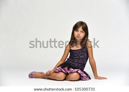 Young girl in a nice dress sitting on the floor looking at the camera