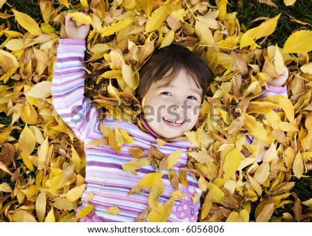 Young Girl in a Pile of Autumn Leaves