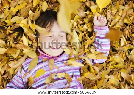 Young Girl in a Pile of Autumn Leaves, Eyes Closed as Leaves Fall on Her