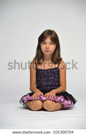 Young girl in a pretty dress sitting on the floor looking straight