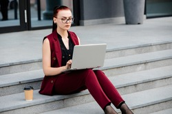 Young girl in a red jacket sitting on the steps and working at a computer. The concept of freelance work