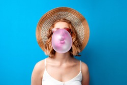 young girl in a sun hat and glasses inflates a bubble gum on a blue isolated background, a woman chews a pink chewing gum in summer clothes, close-up