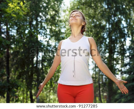 Young girl in a white shirt and red pants doing sport exercises in nature