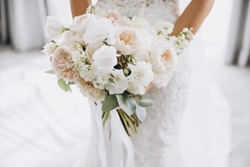 young girl in a white wedding dress holds in her hands a bouquet of flowers and greenery with a ribbon