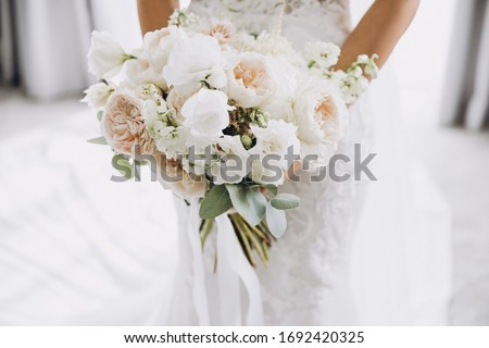 young girl in a white wedding dress holds in her hands a bouquet of flowers and greenery with a ribbon Foto stock ©