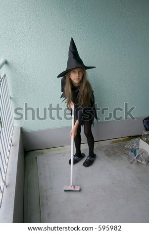 young girl in a witch outfit with broom