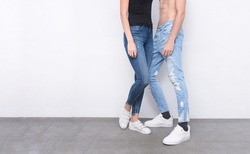 Young girl in black shirt with blue jeans and man in torn blue jeans with white sneaker,shoes on gray background
