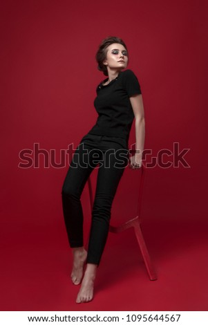 Stock Photo young girl in black suit  red background