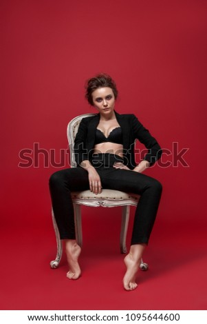 Stock Photo young girl in black suit  red background  armchair