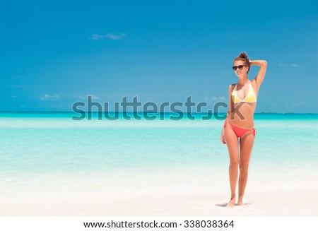 young girl in bright bikini walking at tropical beach