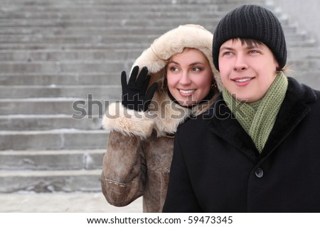 young girl in coat with hood and man in black dress smiling and looking left, half body - stock photo