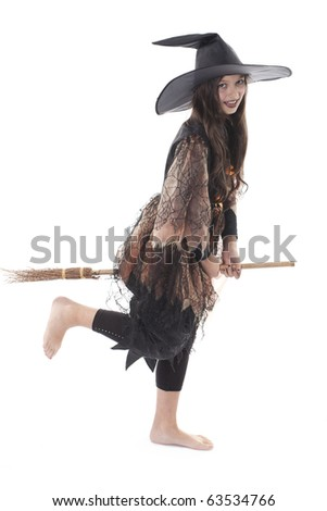 young girl in costume Halloween witch in black dress and hat fly on broom