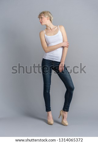 Young girl in denim clothes studio photoshoot. Posing on grey backdrop. Woman in skinny jeans white shirt and high heels shoes front shot in full length