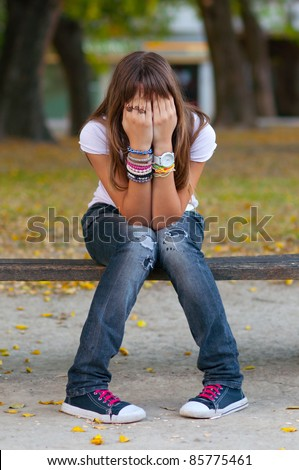 Young girl in fashionable warn out jeans, snickers and t-shirt hides her face with hands while sitting in the park on nice autumn day.