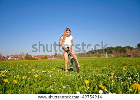 young girl in field standing with her unicycle