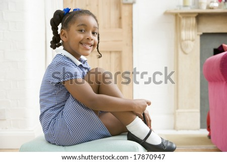 Young girl in front hallway fixing shoe and smiling - stock photo
