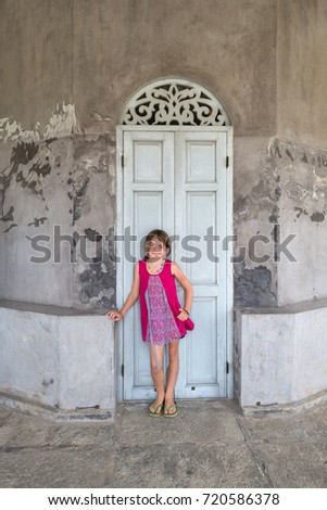 Young girl in front of a old building with blue wooden door