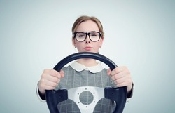 Young girl in glasses with steering wheel, auto concept