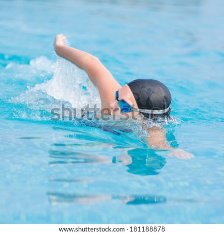 Young girl in goggles and cap swimming front crawl stroke style in the blue water pool