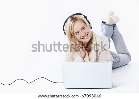 Young girl in headphones with a laptop on a white background