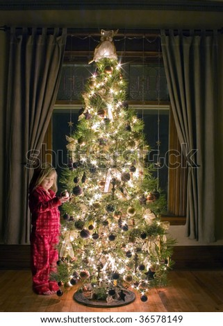 young girl in her pajamas admiring a beautifully decorated Christmas tree