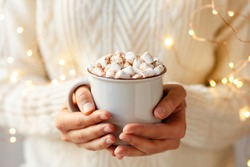 Young girl in knitted white wool sweater is holding a mug with hot chocolate or coffee with marshmallow. Christmas lights on, cozy holiday atmosphere, aromatherapy for cold winter season. Closeup