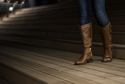 Young girl in leather boots walking down the wooden stairs
