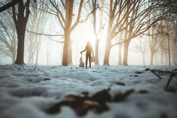 Young girl in moody winter landscape with snow and ice holding a children rabbit toy and vintage suitcase. Sunrise background with a beautiful effects on the snow floor. Woman holding a bunny.