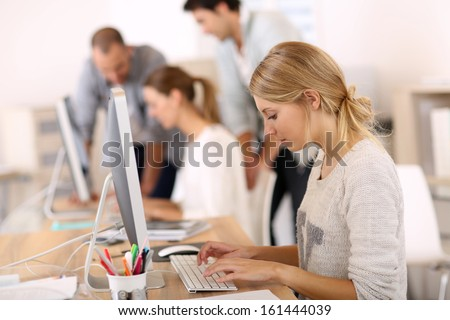 Young girl in office working on desktop computer stock photo