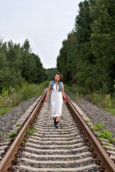 young girl in old-fashioned clothes walking on rails