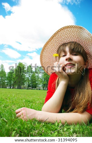 Young girl in panama relaxing with dandelion outdoors