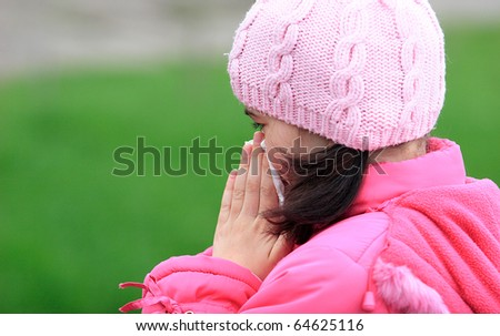 Young girl in pink clothes blow her nose