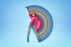 Young girl in pink hoodie and blue ripped jeans, standing with one arm raised and the other arm behind head, with pixel stretch effect on light blue background. Dancing. Creativity. Street fashion.