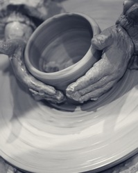 Young girl in process of making clay bowl on pottery wheel. Potter at work. Black and white toned image.