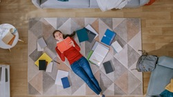 Young Girl in Red Coat and Blue Jeans is Lying Down on a Floor, Reading a Notebook. She Smiles and Laughs. Cozy Living Room with Modern Interior with Carpet, Workbooks and Backpack. Top View.