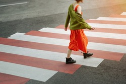 Young girl in red dress and green jacket crosses the road at a pedestrian crossing. metaphor for moving forward, growing up, overcoming difficulties and problems. Stylish fashion catwalk in big city